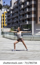 Young attractive woman exercise stretching in urban environment at sunny day