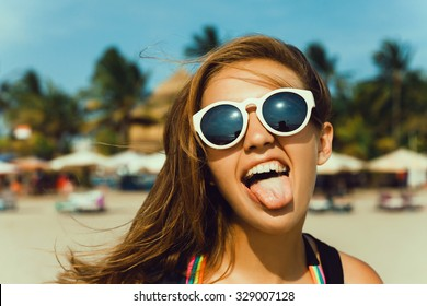 Young attractive woman face over isolated white background,send kiss,red lips,amazing hairstyle after salon,beauty face,going crazy,shows tongue,summer accessories,perfect bronze tan skin,lovely face
