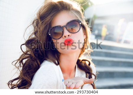 Young attractive woman face over isolated white background,send kiss,with red lips,amazing woman,hairstyle after salon,beauty face,party make-up,summer accessories,perfect bronze tan skin,lovely face