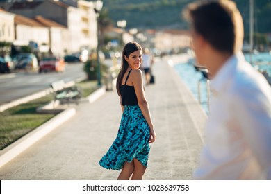 Young attractive woman flirting with a man on the street.Flirty smiling woman looking back on a handsome man.Female attraction.Love at first sight.Meeting ex boyfriend