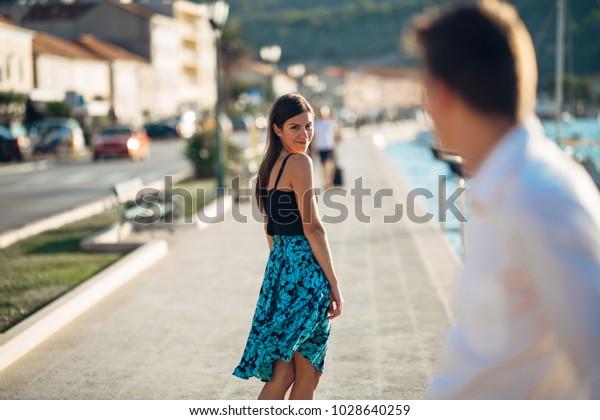 若い魅力的な女性が男性と浮気。男性を振り返る軽薄な笑顔の女性。女性の魅力。一目惚れ。元彼氏との出会い