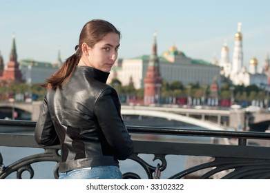 Young attractive woman foreground the kremlin
