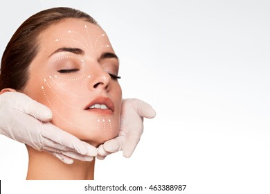 Young attractive woman getting spa treatment. Beautiful girl receiving massage face. Anti aging treatment and plastic surgery concept. Eyes closed with serene expression and white arrows over face