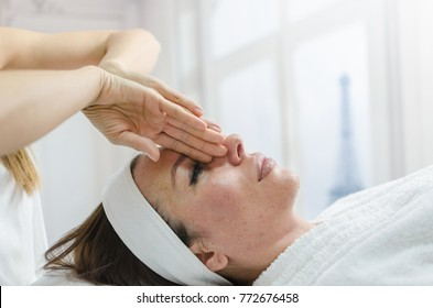 Young attractive woman getting spa treatment over white background in Paris