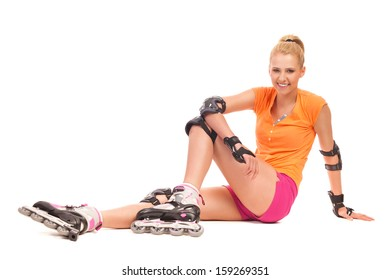 Young attractive woman going rollerblading sitting on the floor. Full length studio shot isolated on white.