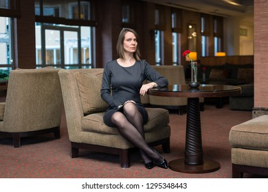 Young attractive woman with grey dress and high heels sitting on an armchair and posing