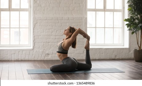 Young attractive woman in grey sportswear, leggings and bra practicing yoga, beautiful girl sitting in Rajakapotasana pose, One Legged King Pigeon exercise, working out at home or in yoga studio