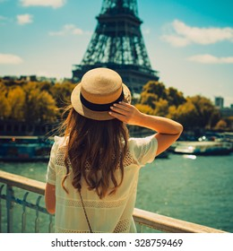 young attractive woman in hat, white dress, red bag poses in front of the Eiffel Tower in Paris. Photo with instagram style filters