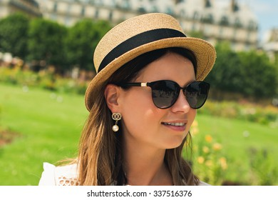 young attractive woman in hat, white dress, red bag and retro camera poses against Paris. Fashion and city style.