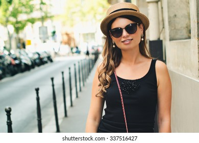 young attractive woman in hat, white dress, red bag poses against Paris. Fashion and city style.