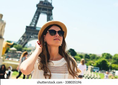 young attractive woman in hat, white dress, red bag and retro camera poses in front of the Eiffel Tower in Paris