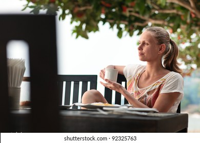 A young and attractive woman having a coffee break in an outdoor restaurant on a beach