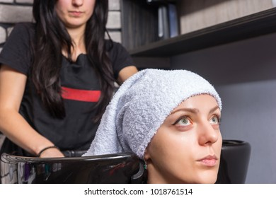 Young attractive woman having her hair wrapped in a towel by female professional stylist in washing sink in beauty salon