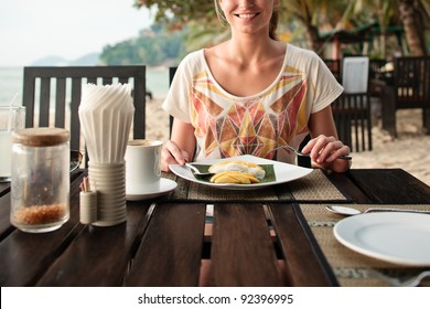 A young and attractive woman having a mango dessert in an outdoor restaurant on a beach