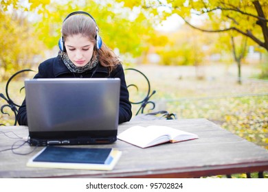 young attractive woman with headphones and laptop computer in park