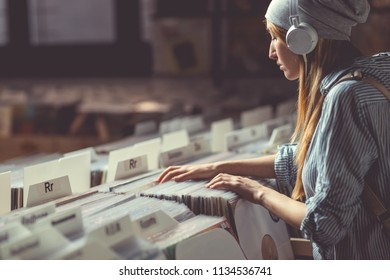 Young attractive woman with headphones in music store