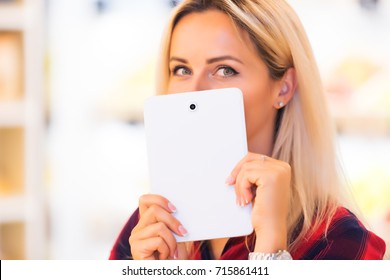 Young attractive woman hides her smile with a tablet computer PC