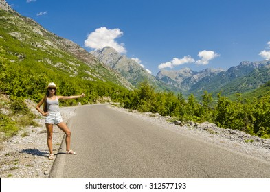 Young attractive woman hitchhiking along empty road