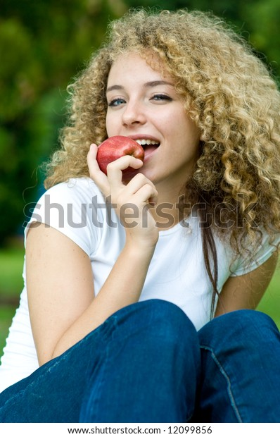 A young attractive woman holding an apple