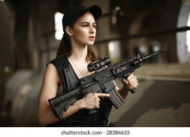 A young and attractive woman holding an assault rifle safely with her finger off the trigger.