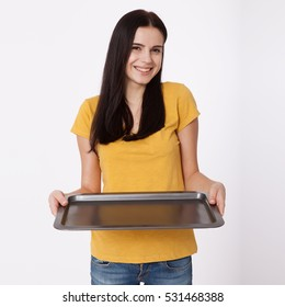 Young attractive woman holding an empty tray isolated on white background. Woman in yellow T-shirt friendly smiles. Blank template for design of the tray.