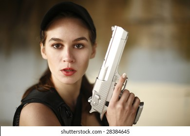 A young and attractive woman holding a fun safely with her finger off the trigger.