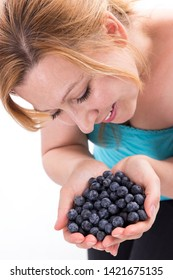 Young attractive woman holds 2 hands full of blueberries
