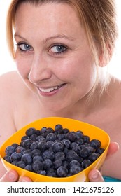 Young attractive woman holds a yellow bowl full of blueberries at the camera