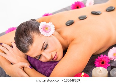young attractive woman hot stone massage wellness  salon healthcare