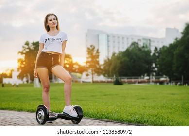 Young attractive woman with hoverboard outdoors in the park at the sunset. Toned