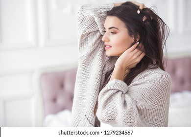 Young attractive woman indoors. Girl on neutral background. Happy woman. Female in the bedroom at home. Close up portrait of beautiful lady.