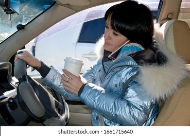 Young attractive woman in jacket driving the car, drinking coffee and talking on phone on a spring day