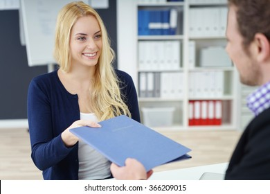Young attractive woman in a job interview handing over a blue folder with her CV to a male business manager with a charming smile