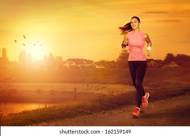 Young attractive woman jogging outdoor on sunset
