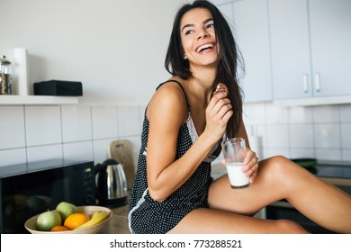 young attractive woman at kitchen in morning, having breakfast, smiling, natural look, drinking milk, eating cookie, laughing, happy, healthy
