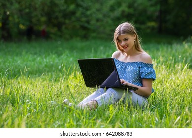 Young attractive woman with a laptop sitting on the grass
