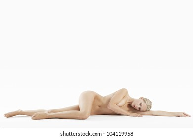 Young attractive woman laying naked on a white background.