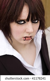 A young and attractive woman with lip piercings and lots of eyeliner wears a suit an stares straight at you!