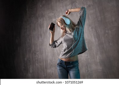 Young and attractive woman listening to music in the mobile app. Girl music lover. Grey clothing and background