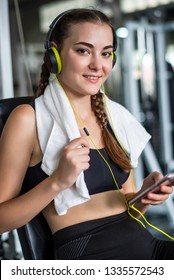 Young attractive woman listening to music by earphones connect to smart phone or cellphone. Relaxation after hard workout in gym