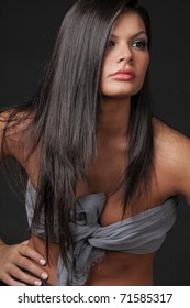 Young attractive woman with long black hair on black background.