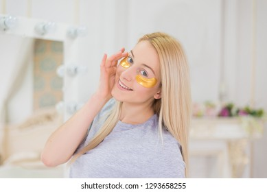Young attractive woman with long blonde hair and mask under eyes looking to the mirror. Beautiful female with natural makeup, have golden collagen patches on fresh facial skin in the bedroom.