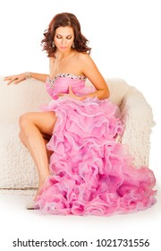 Young attractive woman in long pink dress sitting on a sofa