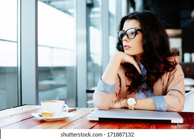 Young attractive woman looking away thoughtfully at her laptop