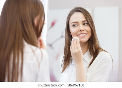 Young attractive woman looking at mirror, cleanses the face with a cotton pad after a shower at the bathroom. Skincare concept.