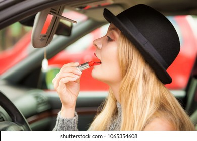 Young attractive woman looking in rear view mirror painting her lips doing applying make up while driving the car.