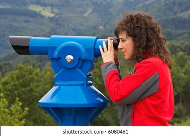A young attractive woman looking through a telescope. Blurred background