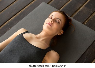 Young attractive woman lying in Dead Body exercise or Corpse pose with her eyes closed, Savasana pose, working out, resting after practice, indoor close up, studio, top view