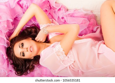 Young attractive woman lying on a pink cape