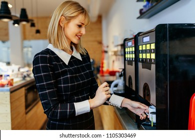 Young attractive woman making a coffee in an office cafeteria